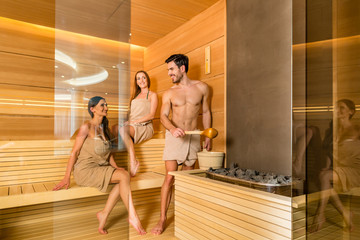 Full length of three young and beautiful people smiling while socializing in a wooden dry sauna heated with charcoals