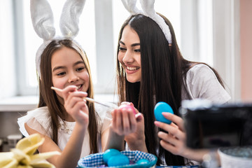 Mother and daughter taking selfie white painted eggs at Easter time.
