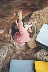 Rock climber climbing overhanging boulder