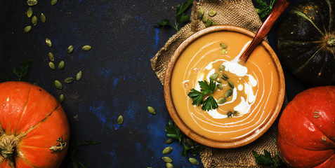 Cream pumpkin soup in a wooden bowl, rustic style, top view