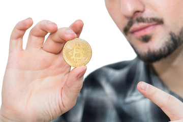 Modern bearded man holding a bitcoin, new cryptocurrency money in his hand and pointing a finger at it.