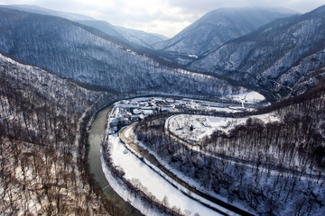 Aerial drone photo of a beautiful monastery in Romania set in a charming winter landscape with snow