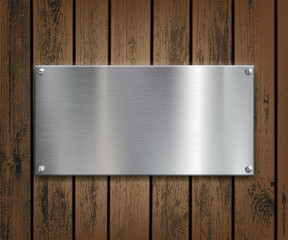 Metal plate on a wooden background.