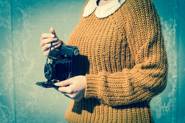 Close-up of young woman's hands taking a photograph with an old retro film camera, Vintage filtered colour effect, Vintage filtered colour effect