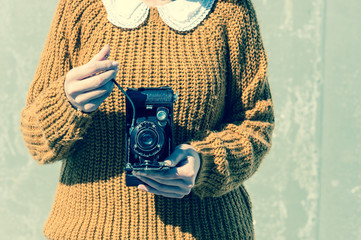 Close-up of young woman's hands taking a photograph with an old retro film camera, Vintage filtered colour effect