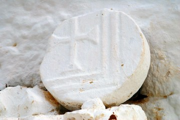 An old stone with Christian symbols carved on it, outside traditional country church at Vathi village. Kalymnos island, Dodecanese islands, Greece.