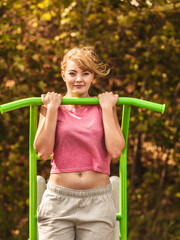 Active woman exercising on ladder outdoor.