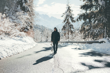Skateboarder standing in the middle of the icy road  between the mountains, surrounded by the snow