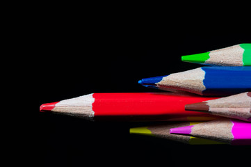 Sharp red pencil in focus, conceptual leadership image on black background.