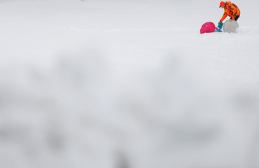A man helps a child after sledding down a hill following a snowstorm in Huntington Station