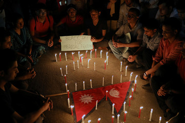 People including Nepali students of University of Dhaka light candles in memory of the victims of the US-Bangla aircraft crash in Nepal, in Dhaka