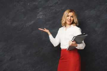 Smiling businesswoman pointing away