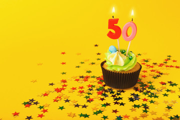 50th birthday cupcake with candle and sprinkles