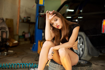 A beautiful lady sits on the tire in the garage. One hand holds the head in the second hand with a wrench. In the background a black car. The girl is upset