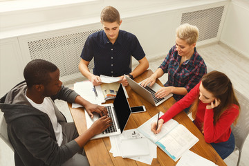 Group of diverse students studying at wooden table