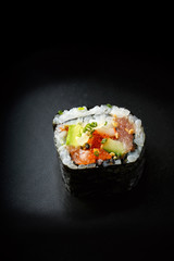 one Japanese roll with tuna, avocado, flying fish roe on a black background. delicious fast food with a place for writing.
