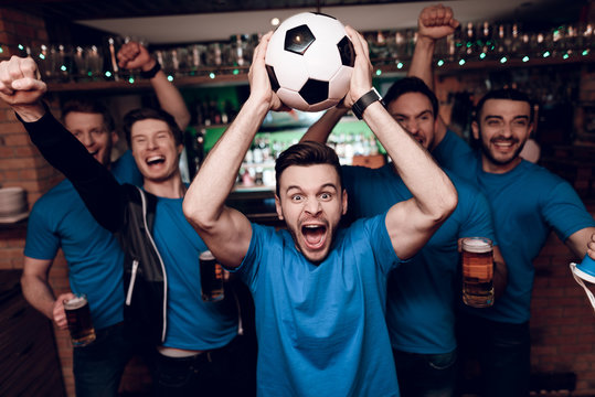 Five soccer fans drinking beer celebrating and cheering at sports bar.