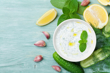 Traditional sauce tzatziki from greek yogurt with ingredients cucumber, mint, dill, lemon and garlic on rustic table top view.
