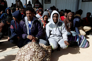 Migrants sit at a naval base after they were rescued by the Libyan coast guard in Tripoli