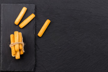 Crispy bread sticks on black stone background with copy space