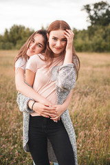Two young women are hugging on the field at evening