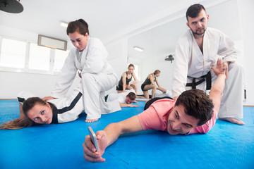 Adults taking photos while practicing taekwondo holds