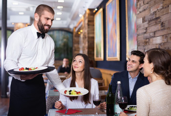 Waiter with dishes serving man and woman friendly company indoors