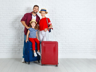 concept travel and tourism. happy family with suitcases near   wall.