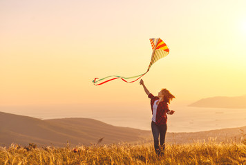 Happy young woman running with kite on glade at sunset in summer.