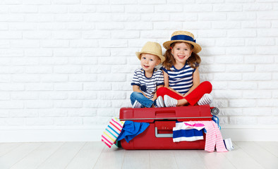 happy laughing children  with suitcase going on a trip