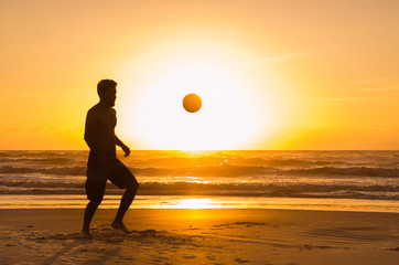 Great concept of soccer, man playing soccer on the beach in golden hour, sunset. Making keepie uppie.