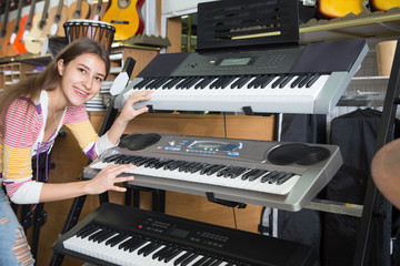 Girl selecting synthesizer in shop