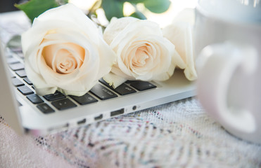 Roses laying on laptop keyboard next to coffee cup