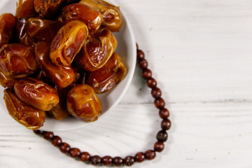 Dates fruit and rosary on white wooden table. Top view
