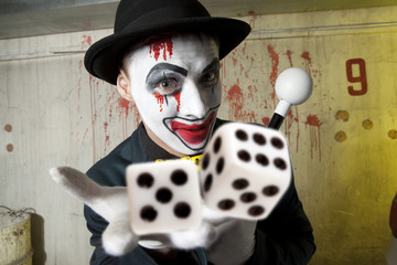 Evil clown playing with dice