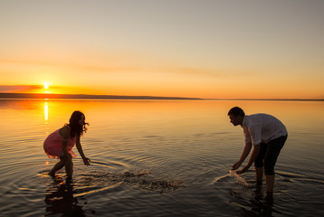 Young couple is playing the water on summer beach. Sunset over the sea.Two silhouettes against the sun. Just married couple in romantic love story. Man and woman having fun and laughing in honeymoon.