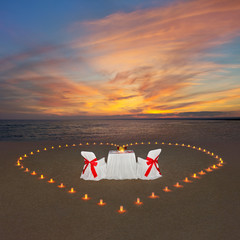 Romantic dinner with candles heart at sunset ocean beach. Proposal, wedding or honeymoon concept.