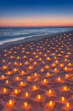 Sunset ocean sandy beach decorated with lot flare lights of candles. Romantic sea vacation or honeymoon concept vertical background.