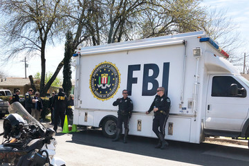 Law enforcement personnel including FBI agents are seen near a home that was hit with a parcel bomb in Austin