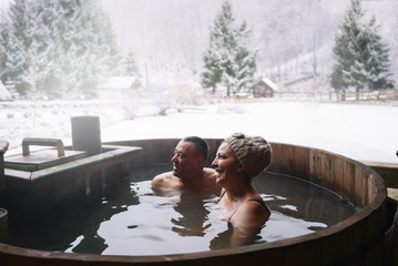Cheerful adult couple in plunge tub