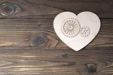 heart, gears on a wooden background. love. feelings. symbol.