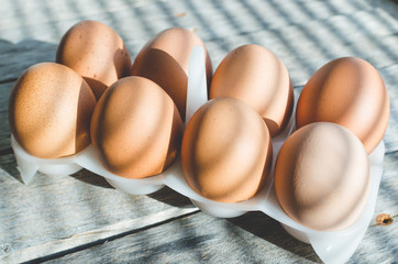 Chicken eggs on a wooden old table in the early sun.