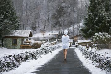 Woman in bathrobe walking to forest