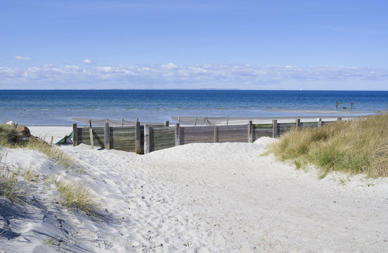 Laesoe / Denmark: Beach access with wooden sand fence in Vesteroe Havn on a sunny day in April