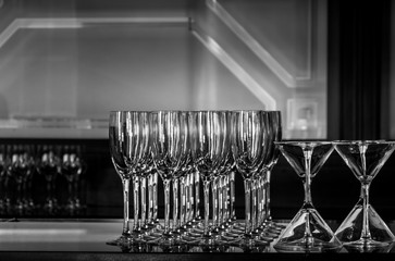 Clean wine and martini glasses sit shimmering on a bar in the right side. A geometric pattern is embedded in the mirror. Horizontal image in black and white.