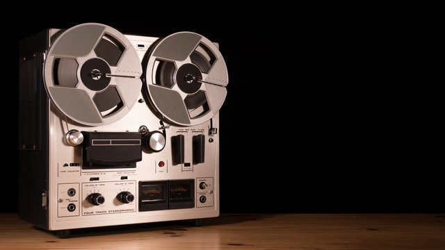 Reel to Reel taperecorder playing music isolated on black background and space for copy