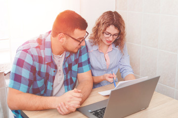 Young  couple talking at home in the kitchen with laptop papers, cheerful man and woman holding documents excited by planning new purchase, having fun enjoying positive news in letter