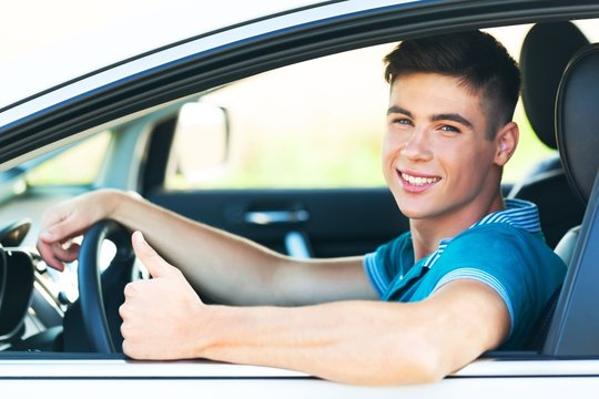 Portrait of Young Man in his Car Showing Thumbs Up