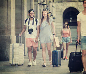 Happy couple tourists taking walk on summer day