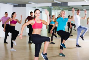 vigorous men and ladies dancing aerobics at lesson